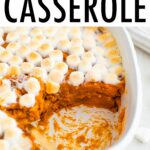 Sweet potato casserole topped with marshmallows. A spoon is in the casserole scooping a portion out.