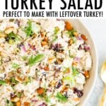 Bowl of creamy turkey salad with celery, cranberries and almonds.