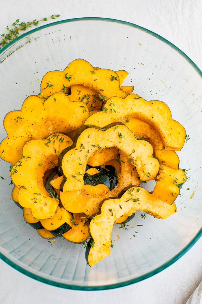 Acorn squash slices in a bowl with herbs, salt and pepper.