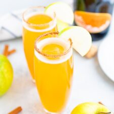 Two tall glasses of apple cider mimosas with a cinnamon sugar rim and an apple slice for garnish.