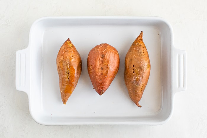 Three baked sweet potatoes in a baking dish.