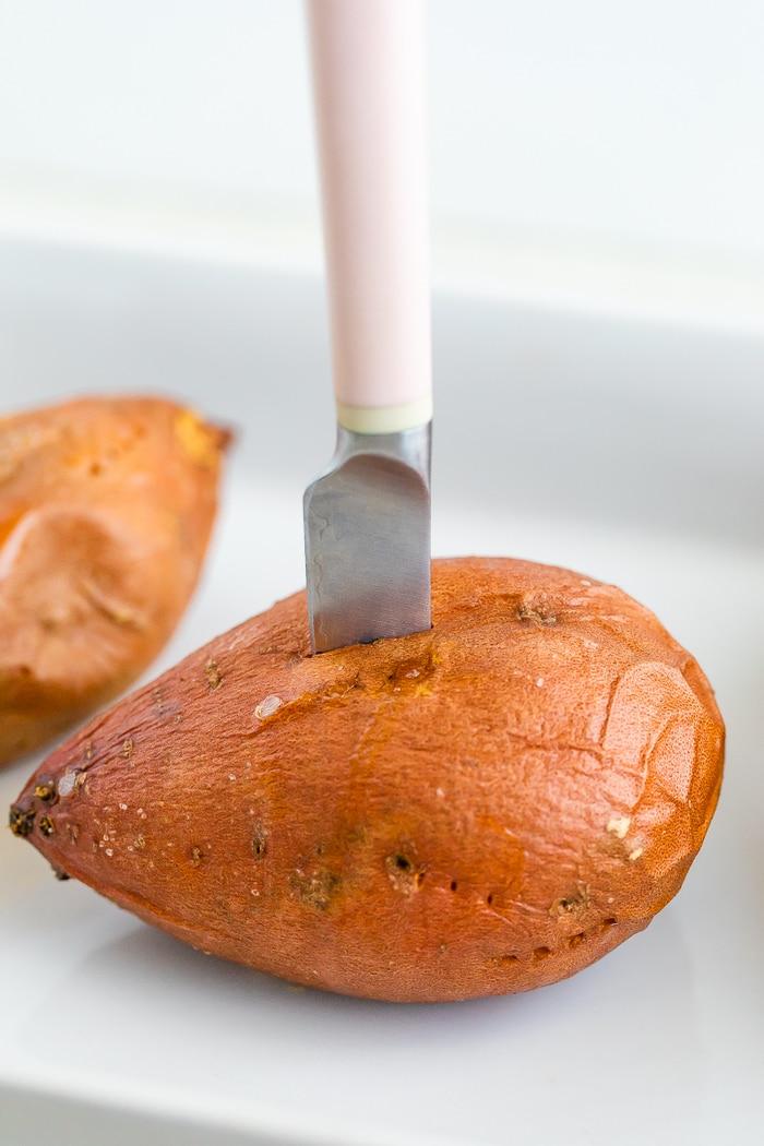 Knife cutting a baked sweet potato open