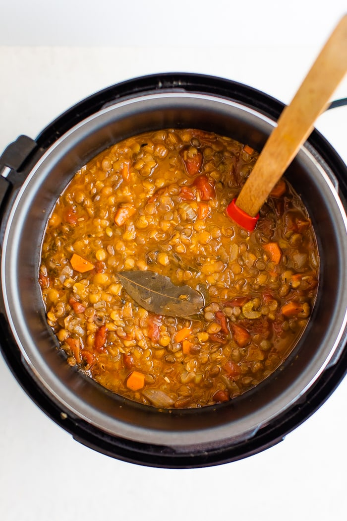 Lentil soup in an instant pot. A wood spoon is in the pot.