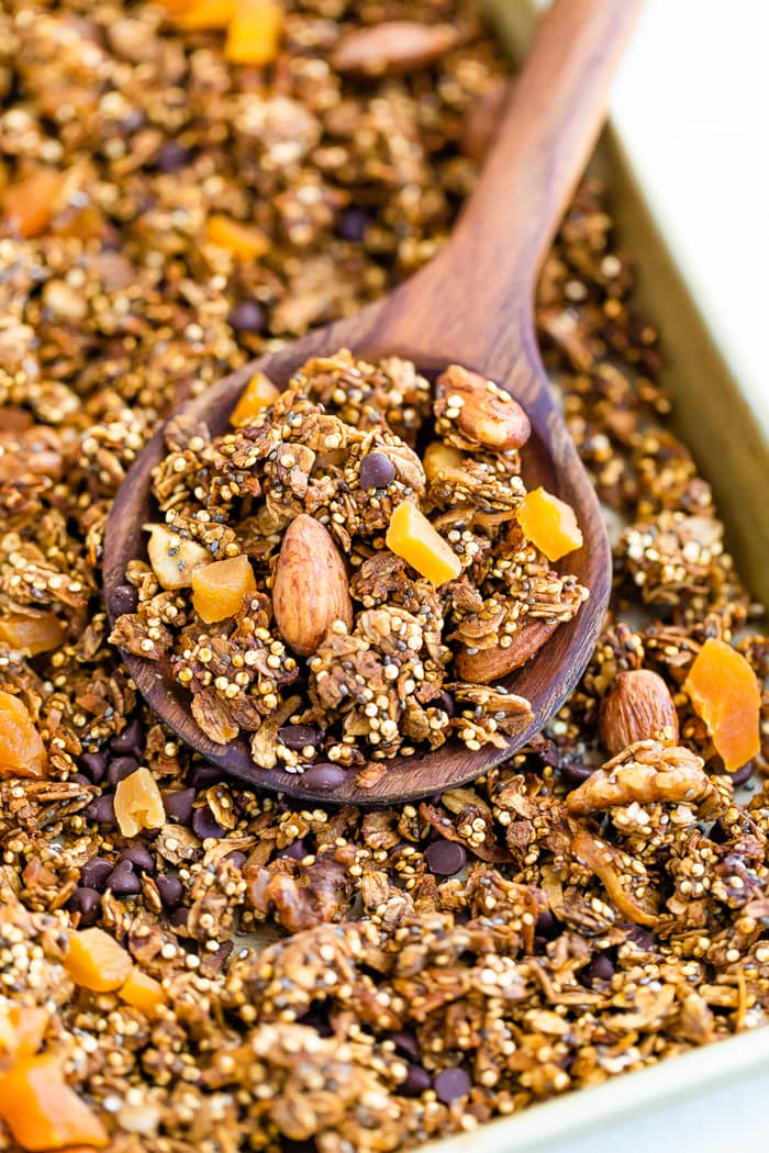Wood spoon scooping up quinoa granola made with chocolate chips, nuts and dried fruit. Granola is on a baking sheet.
