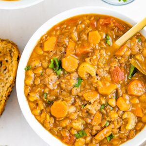 Bowl of lentil soup with celery and carrots. Beside the bowl is a slice of bread and parsley.