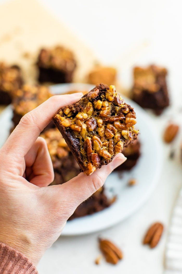 Hand holding a brownie topped with pecan pie topping.