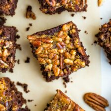 Pecan pie brownies on a table surrounded by pecans.