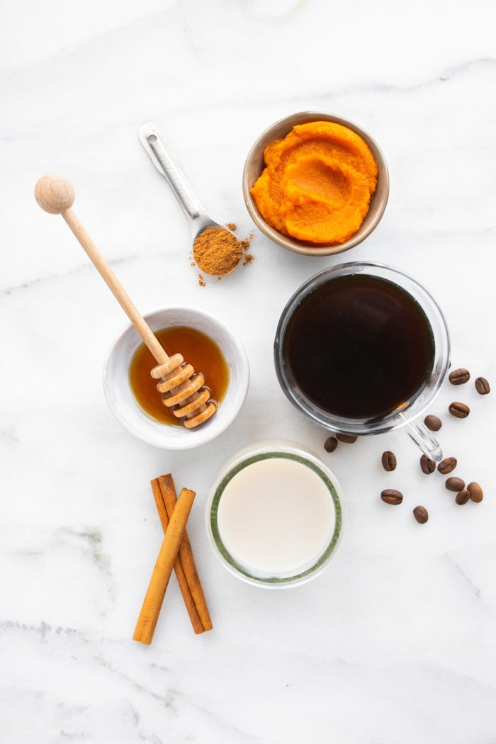 Ingredients to make a homemade pumpkin spice latte on a marble countertop: pumpkin, pumpkin spice, coffee, almond milk and maple syrup..
