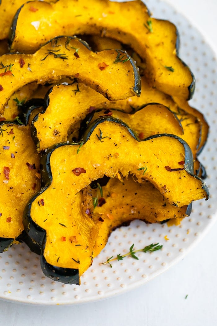 Slices of roasted acorn squash on a plate and seasoned with spices.