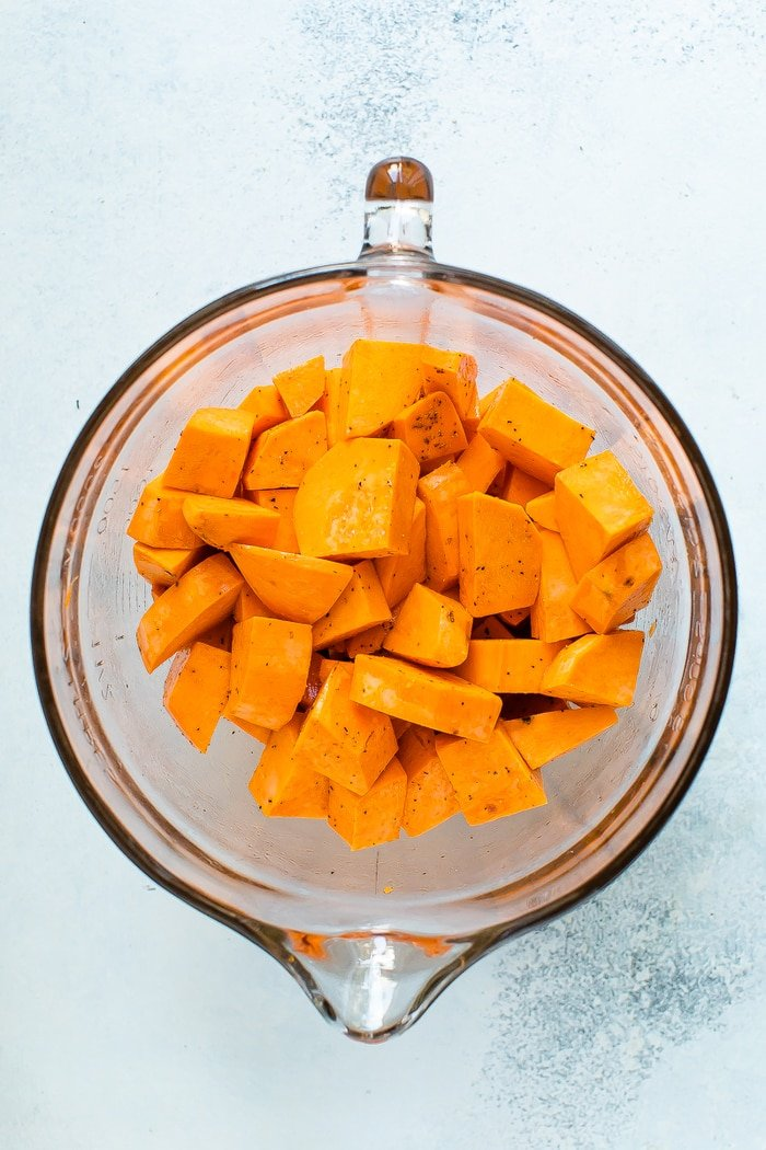 Glass mixing bowl with sweet potato chunks seasoned with pepper.