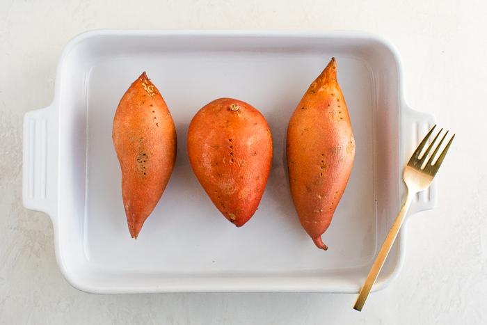 Three sweet potatoes pierced with a fork in a baking dish.