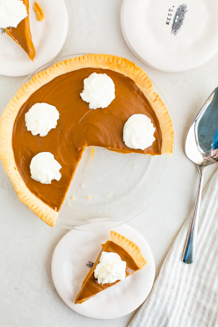 Sweet potato pie topped with whipped cream. A slice is taken out of the pie and is on a plate.