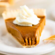 Slice of sweet potato pie topped with whipped cream. A bite is taken out of the pie.