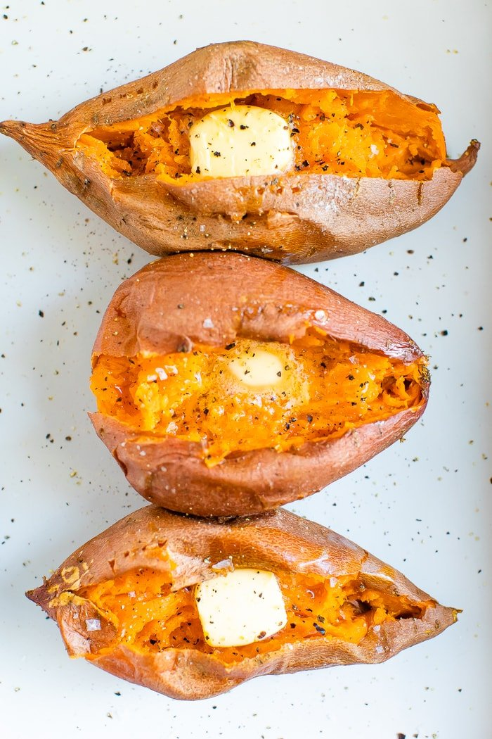 Three baked sweet potatoes topped with butter, salt and pepper.