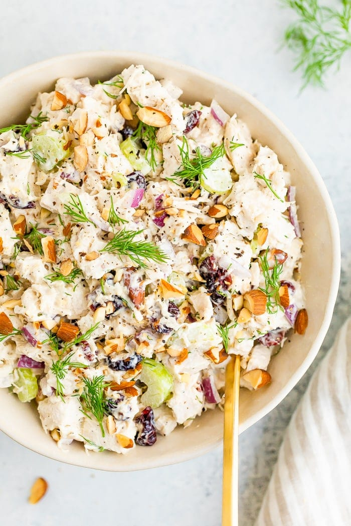 Bowl full of turkey salad topped with fresh dill and chopped almonds.