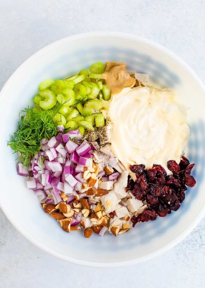 Mixing bowl with mayo, chopped turkey, celery, cranberries, onions and herbs.