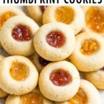 Close up photo of thumbprint cookies with raspberry and orange jams.