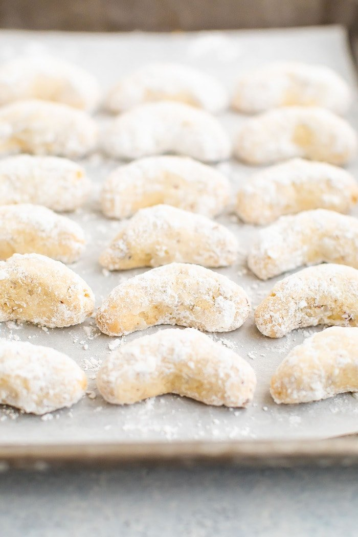 Crescent cookies lined up on a cookie sheet.