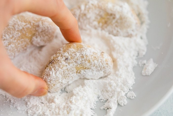 Hand rolling a crescent cookie in powdered sugar.