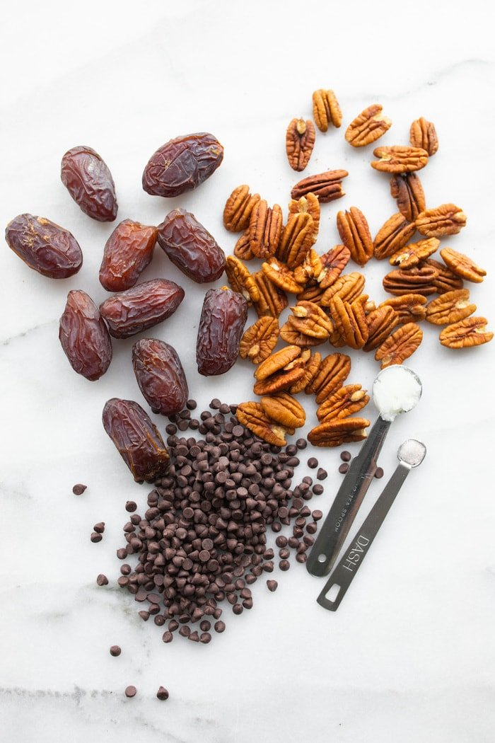 Dates, pecans, chocolate chips, coconut oil and sea salt on a marble table top.