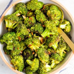 Bowl with roasted broccoli topped with red pepper flakes.