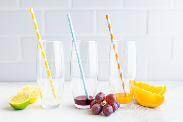 Three glasses with paper straws and a little bit of electrolyte powder mixed with water.