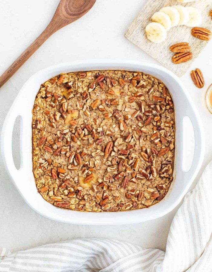 Maple pecan baked oatmeal in a white baking dish with bananas and pecans.