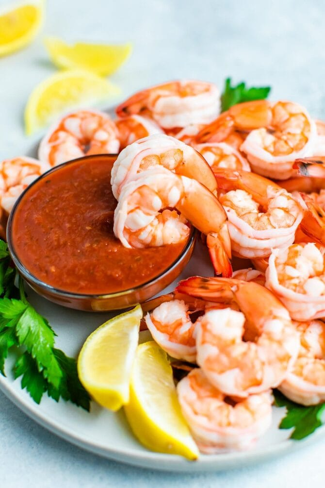 Poached shrimp on a plate with cocktail sauce and garnished with lemon and parsley.