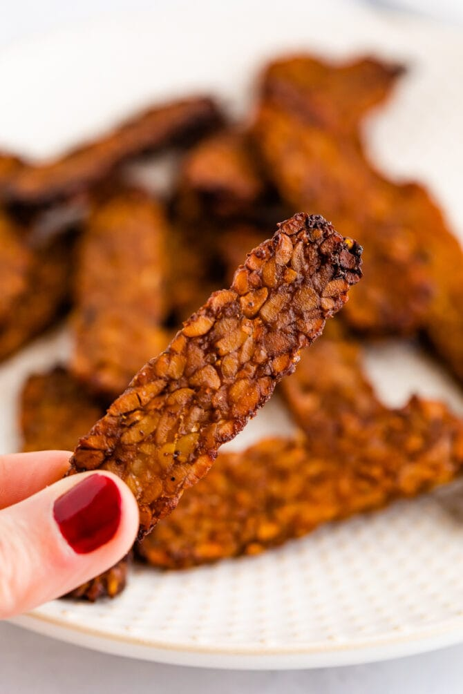Hand holding a slice of homemade tempeh bacon.