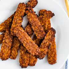Crispy slices of tempeh bacon on a plate.