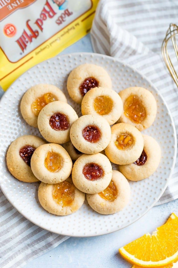 Almond flour thumbprint cookies on a polka dot plate. Some have raspberry jam and some have orange marmalade.