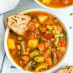 Bowl of vegetable soup served with slices of bread.