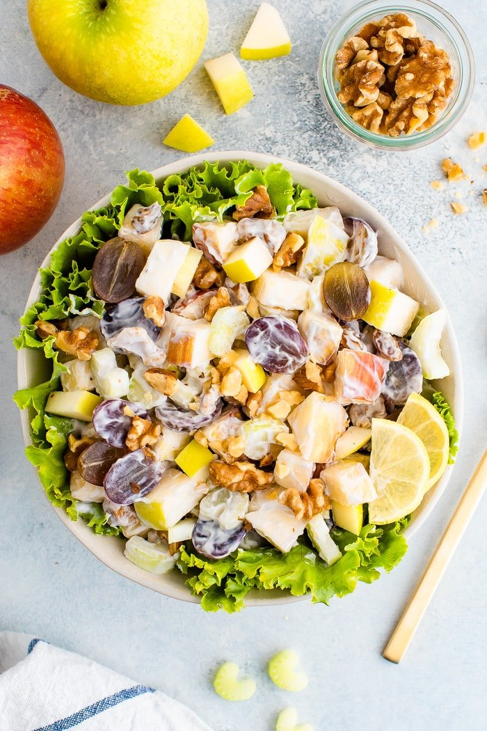 Waldorf salad served in a bowl over lettuce. Apples, walnuts and celery are around the bowl.