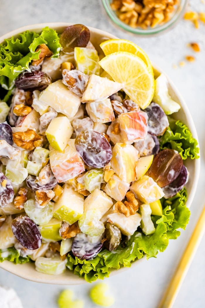 Waldorf salad served in a bowl over lettuce garnished with lemon.