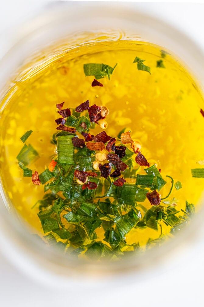 Olivenöl, Essig, Knoblauch, Paprikaflocken und Frühlingszwiebeln in einem Glas.
