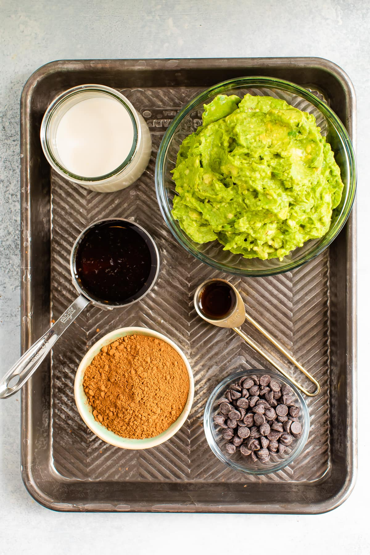 Ingredients for avocado pudding on a tray - almond milk, maple syrup, cocoa powder, avocado, vanilla and chocolate chips