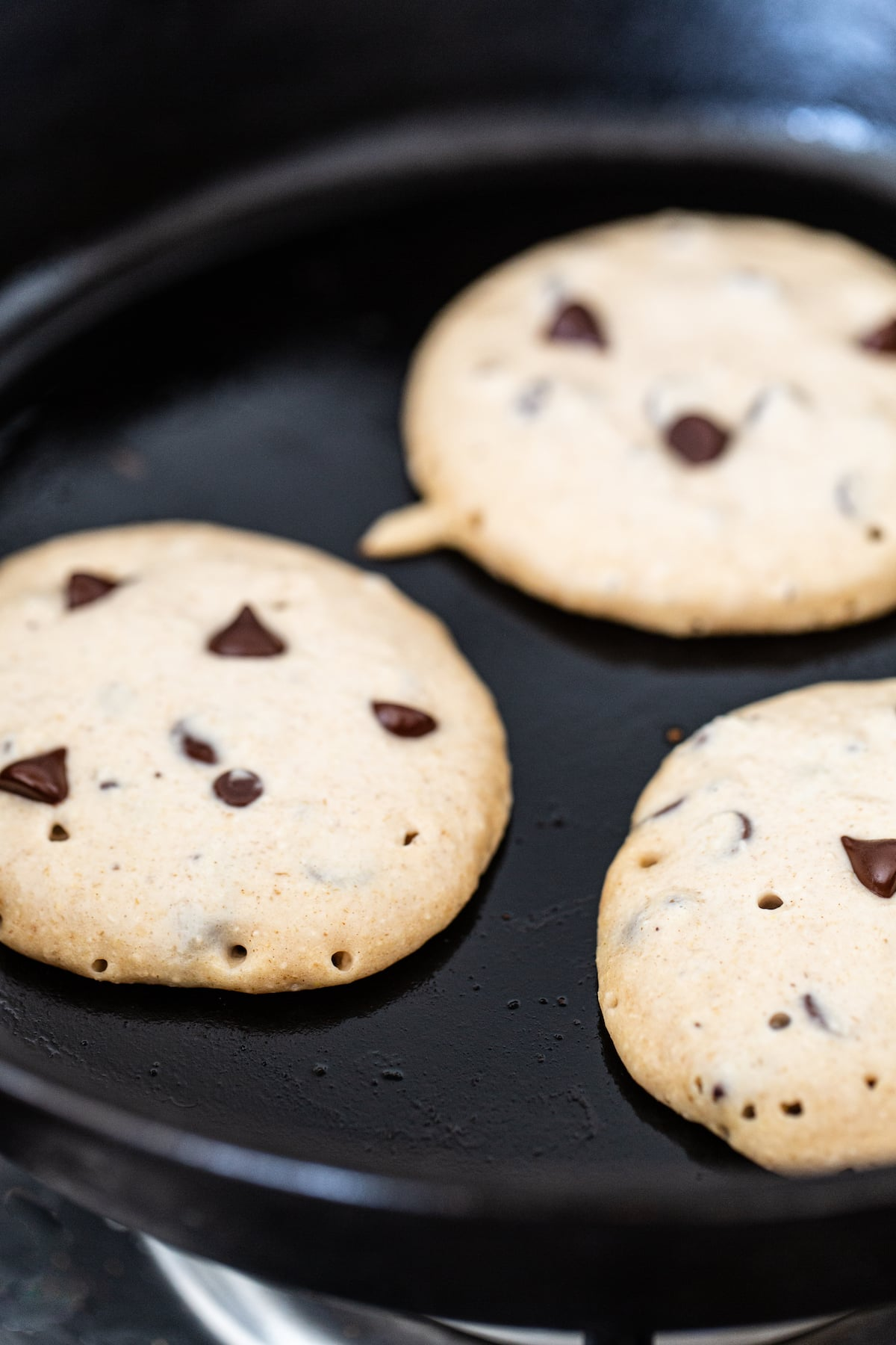 Chocolate chip pancakes in a frying pan.