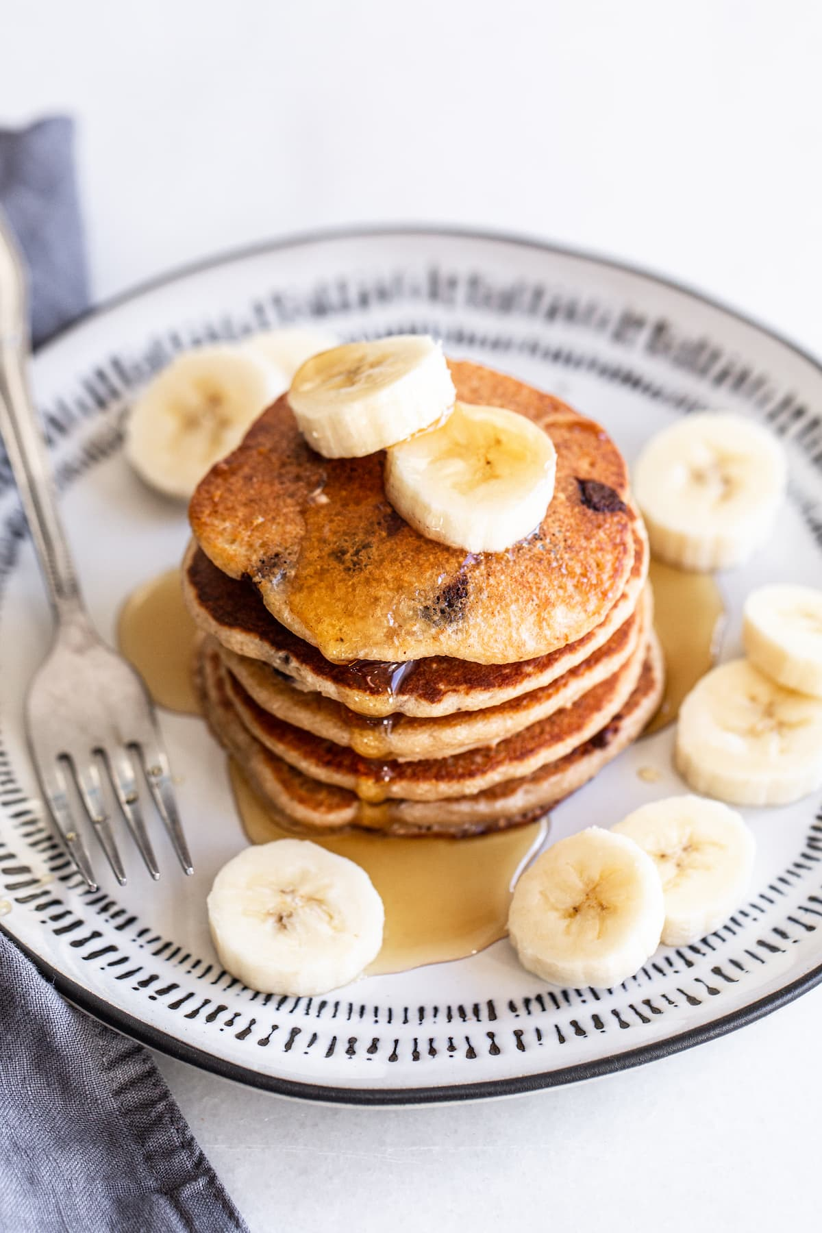 Stack of banana chocolate chip pancakes topped with banana slices and maple syrup.