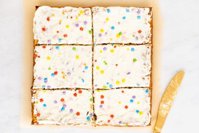 Birthday cake baked oatmeal topped with frosting and sprinkles sliced into 6 slices.