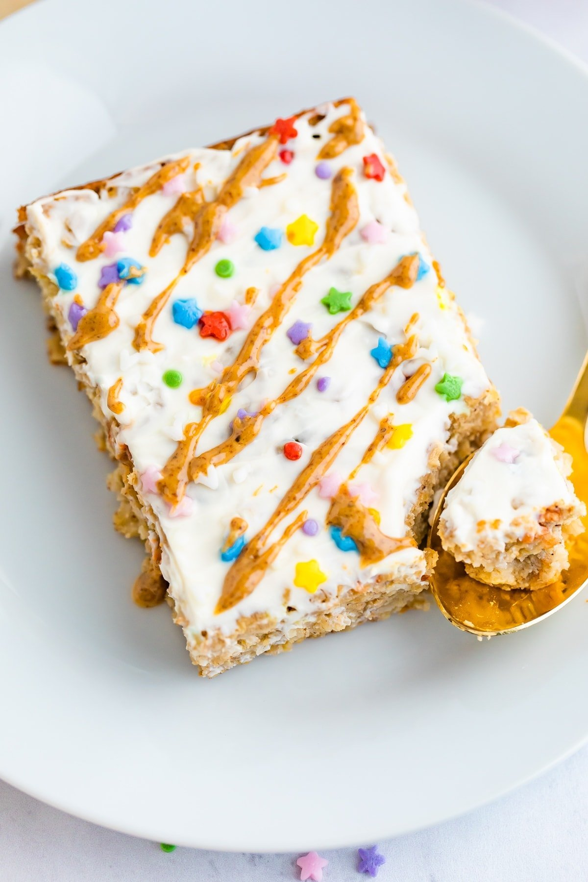 Slice of birthday cake baked oatmeal topped with frosting, nut butter drizzle and sprinkles. A spoon has taken a bite out of it.