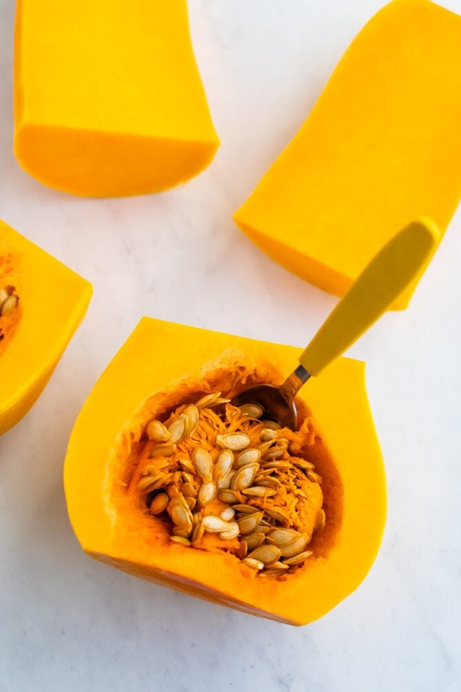 Halfways cut butternut squash with a spoon in the seeds and guts.