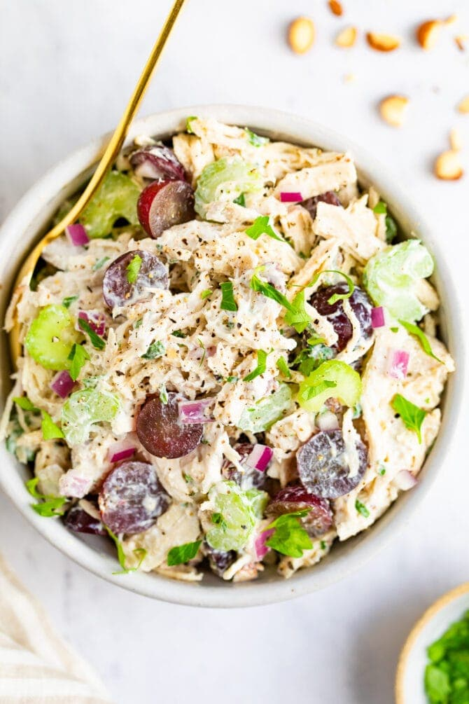 Bowl of chicken salad made with celery and grapes.