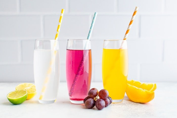 Three glasses of homemade different flavor soda with paper straws.