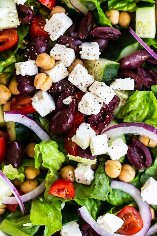 Close up photo photo of a greek salad with romaine, kalamata olives, tomatoes, chickpeas, feta, cucumber and onions.