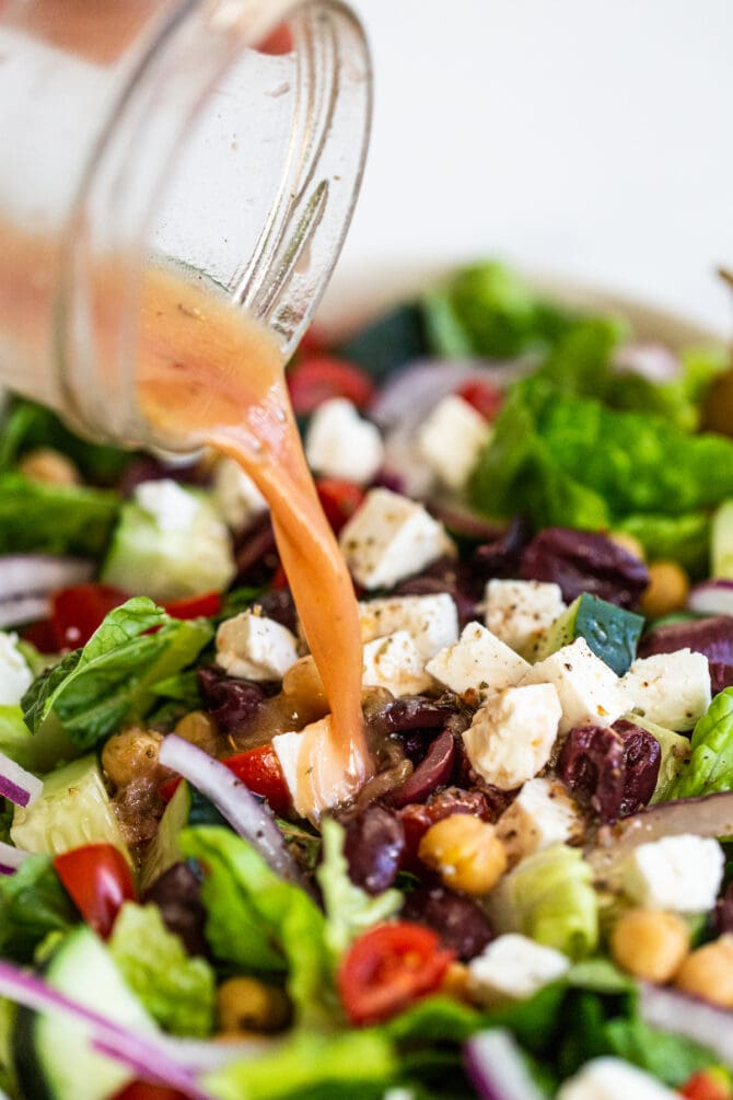 Homemade greek salad dressing being drizzled over a Greek salad.
