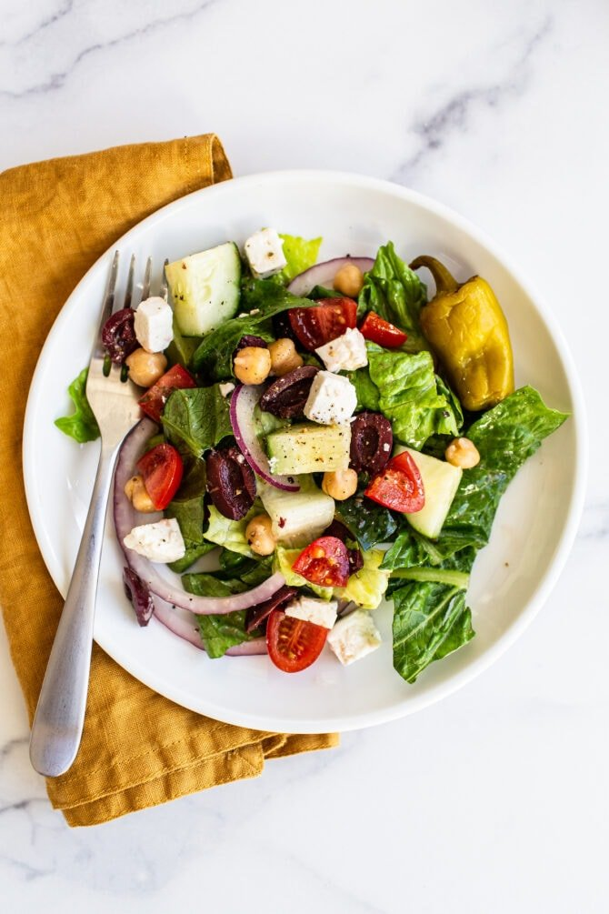 Plate and fork with greek salad. Yellow cloth napkin is below the plate.