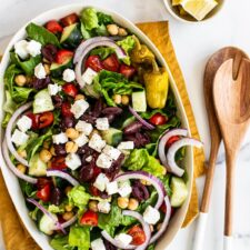 Oval platter with a greek salad. Salad tongs and lemon wedges are beside the platter.