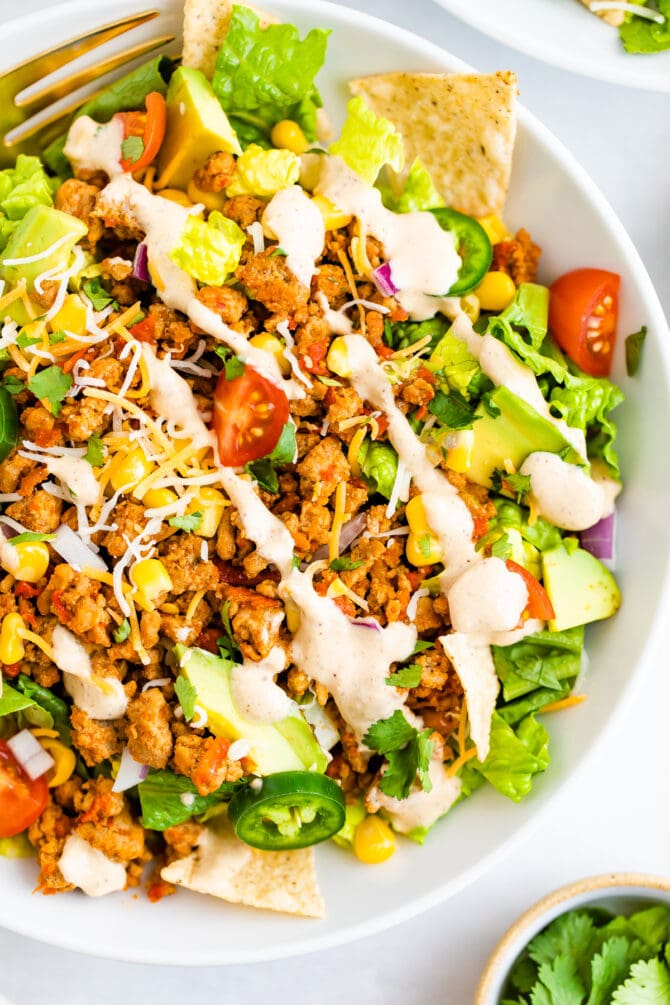 Taco salad topped with ground turkey, avocado, corn, peppers, chips, dressing and tomatoes.