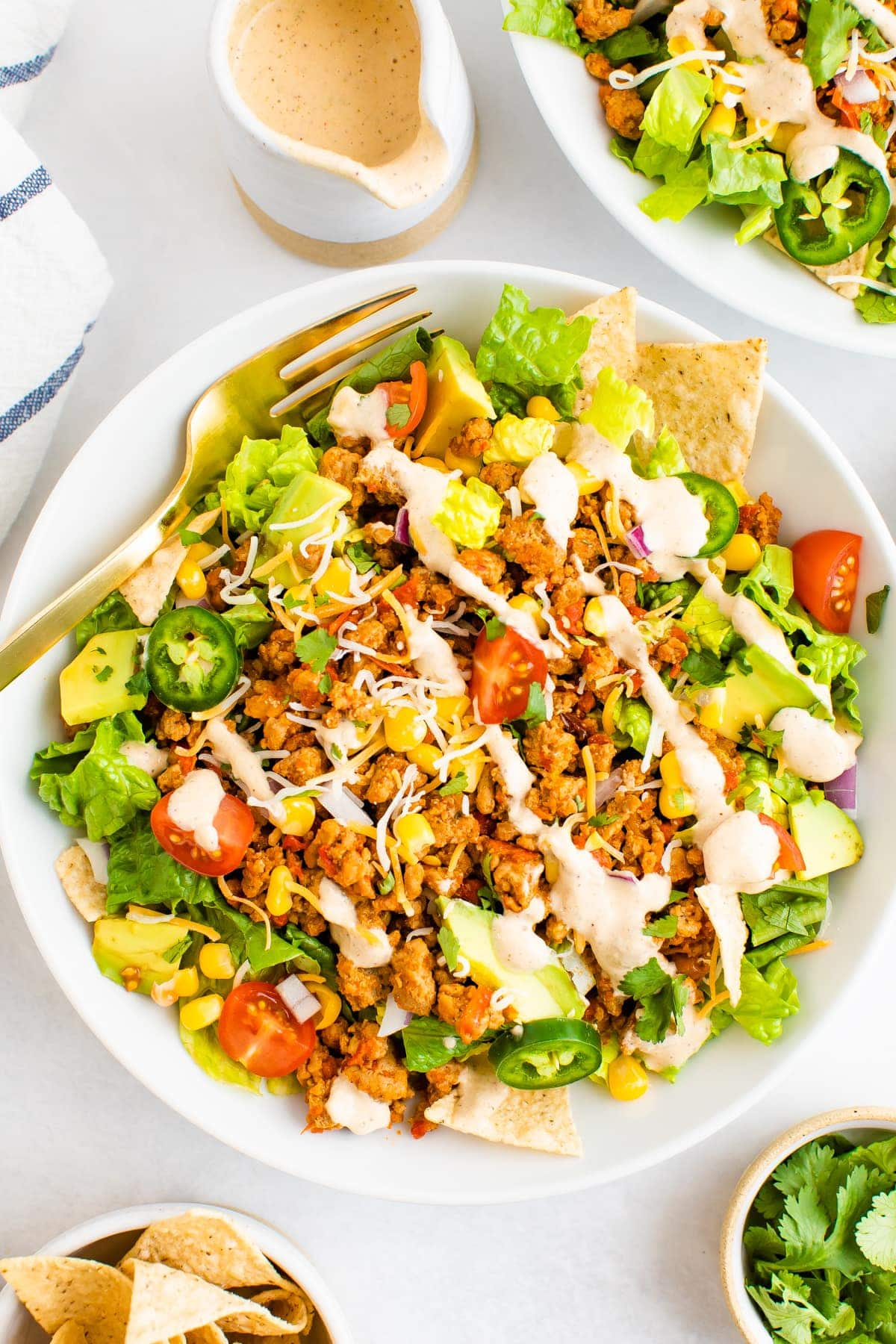 Taco salad topped with ground turkey, avocado, corn, peppers, chips and tomatoes and a southwest dressing.