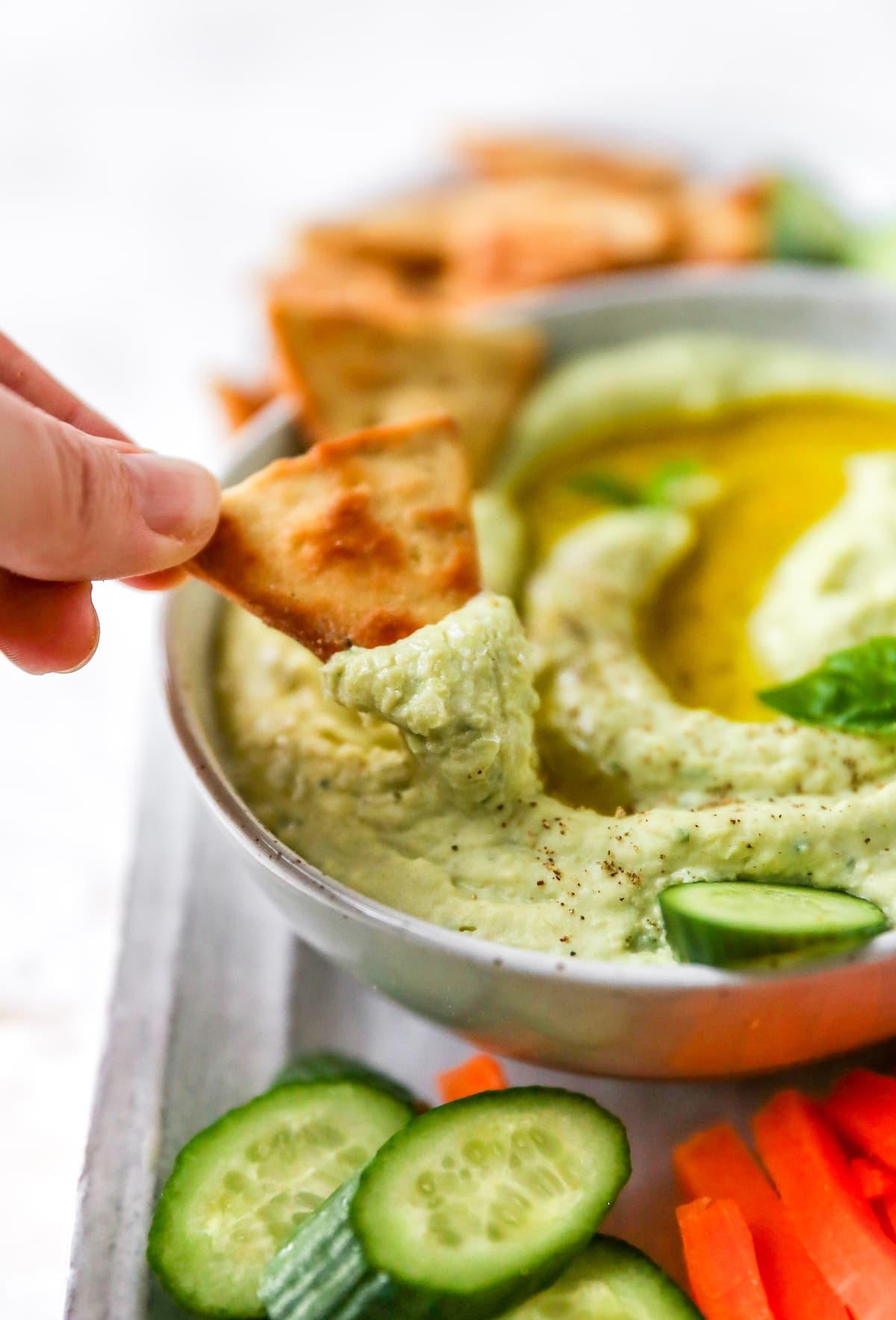 Hand dipping a pita cracker into a bowl of lima bean hummus.